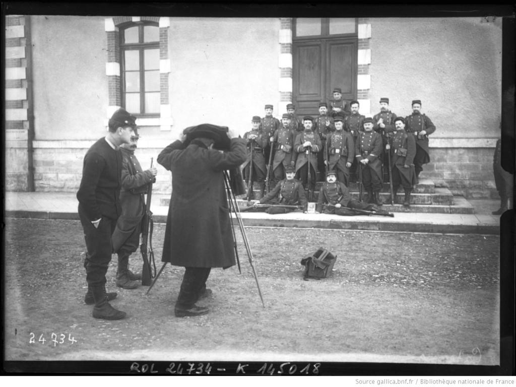 Un photographe photographiant un groupe de soldats. Photographie de l'agence Rol, 1912. Gallica/BnF